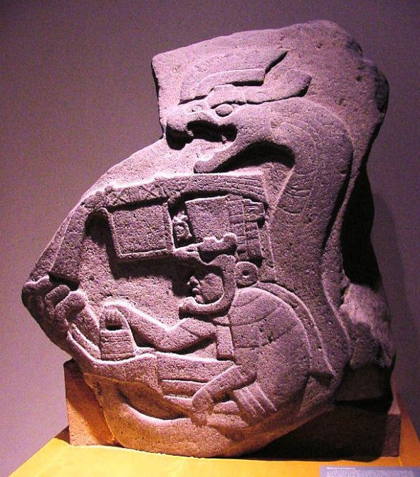 Mission: Atlantis picture. Photo of stone carving of Mesoamerican feathered serpent surrounding human.