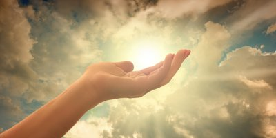 Hand holding the sun, symbolic of spirituality
